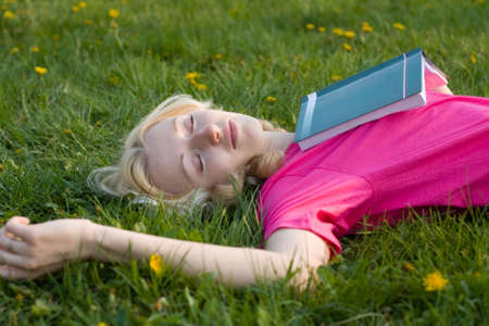 lay: Sleeping girl with a book on the grass