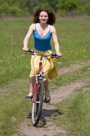 happy girl goes by bicycle photo