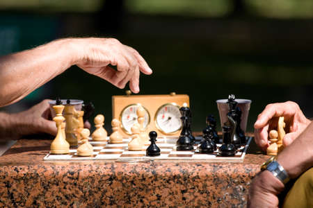 Chess board and hands of people in details photo