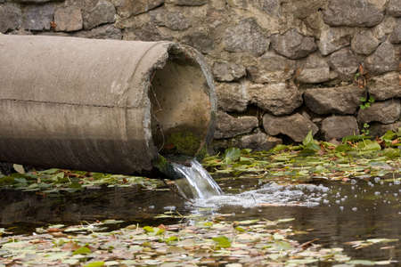 sewage pipe polluting the river photo