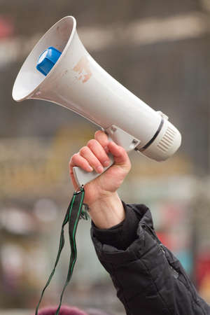 bellowing: human hand holding megaphone Stock Photo