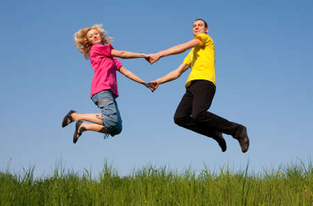 emotional freedom: jumping couples on the  meadow Stock Photo