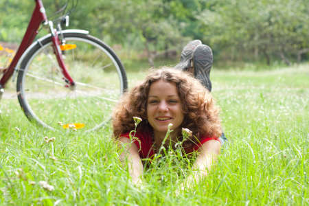 beautiful girl with a bicycle rests on a grass photo