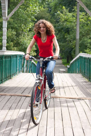 happy girl goes by bicycle on a bridge photo