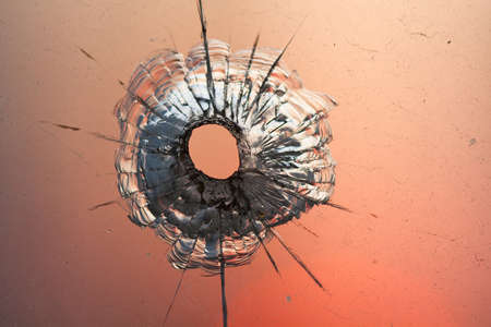 bullet hole in window on the background sunset sky photo