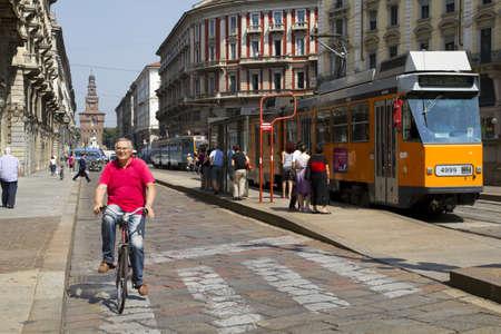 senda peatonal: MILAN, Italia - el 10 de junio de 2010: el hombre va en bicicleta a trav�s de un paso de cebra en Mil�n. Detr�s de su Sforza castillo y antiguo tranv�a naranja. 10 De junio de 2010, en Mil�n, Italia.