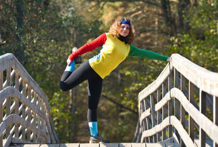 Beautiful young woman doing stretching exercise on a bridge photo