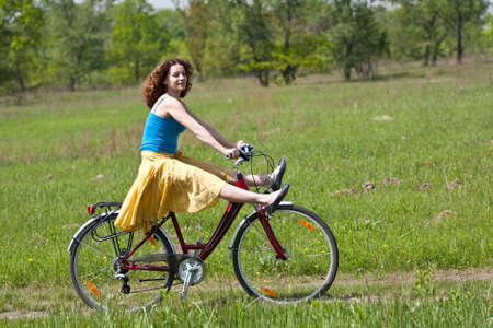 beautiful girl goes by bicycle photo