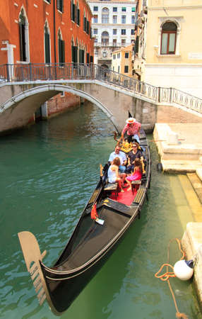 VENICE, ITALY - JUNE 12: Tourists travel  on gondolas at canal near a bridge on June 12, 2010 in Venice, Italy .  The gondola is a traditional, flat-bottomed Venetian rowing boat, well suited to the conditions.