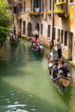 gondolas: VENICE, ITALY - JUNE 12: Tourists travel  on gondolas at canal near a bridge on June 12, 2010 in Venice, Italy .  The gondola is a traditional, flat-bottomed Venetian rowing boat, well suited to the conditions.  Editorial
