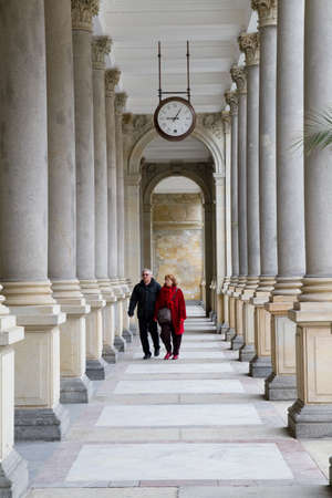 carlsbad: KARLOVY VARY, CZECH REPUBLIC - MAY 4:Tourists go on a corridor between columns  in Karlovy Vary on May 4,2010 in Karlovy Vary,Czech Republic. Carlsbad is famous spa center .