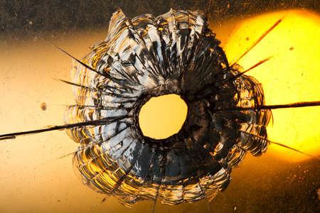 bullet hole in window on  sunset  photo
