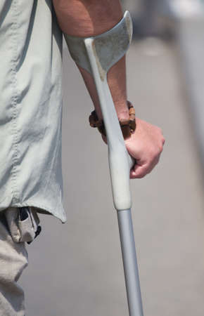 displace: Male  hand holding a crutch in the street