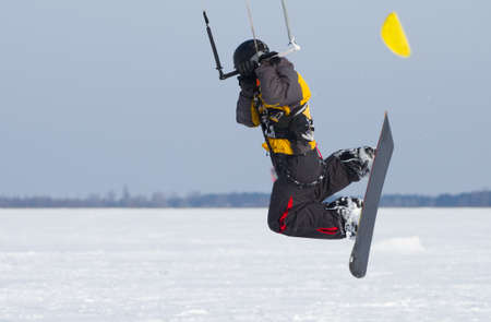 kiting: Snowkiting on a snowboard on a frozen lake