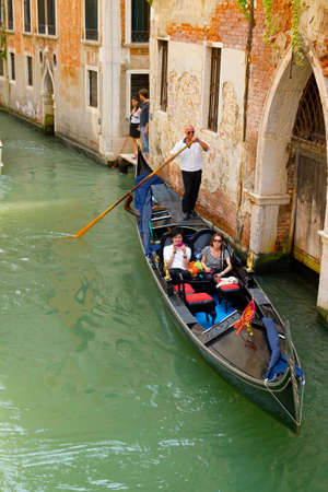 VENICE, ITALY - JUNE 12: Tourists travel on gondolas at canal near a bridge on June 12, 2010 in Venice, Italy . The gondola is a traditional, flat-bottomed Venetian rowing boat.