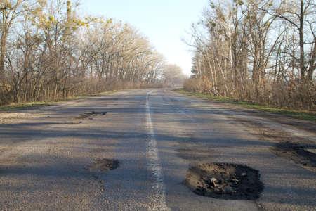 Bad road in holes after winter in Ukraine.