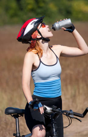 The girl by bicycle drinks water photo