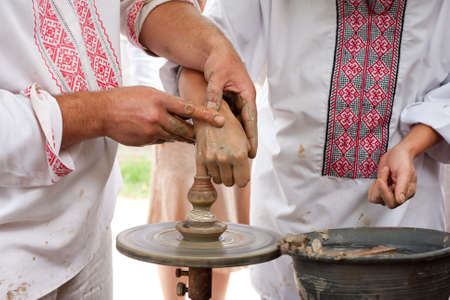 Ukrainian master teaches pottery to boy  photo