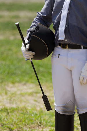 jockeys: Jockey in uniform with a whip and helment