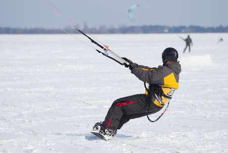 snowkiting: Snowkiting on a snowboard on a frozen lake