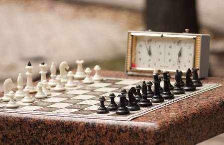 Chessboard with chess and timer in the park Stock Photo