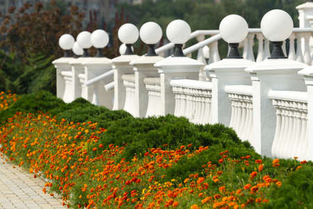 Beautiful white fence with lanterns and flowers photo