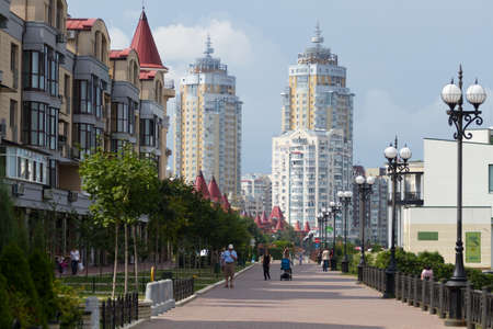 KYIV, UKRAINE - AUGUST 17,2012:People go for a walk on the embankment of the river Dnepr in modern in a district Obolon in Kyiv , Ukraine .