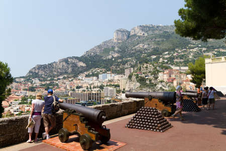 MONACO - JUNE 10, 2010: Tourists stand beside old canons near the Princes Palace of Monaco .