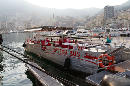 MONACO - JUNE 10, 2010: Ecological electric water bus Bateau bus in a harbour with tourists in Monaco .