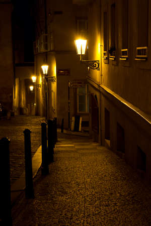 Narrow alley with lanterns in Prague at night ,  Czech Republic .