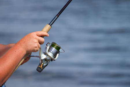 Hand of Fisherman`s  holding fishing rod over the blue water photo