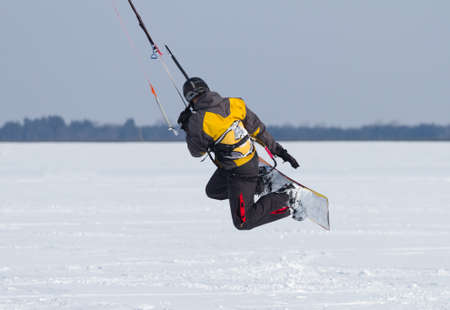 kiting: Man winter snowkiting on a frozen lake