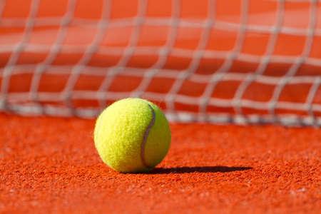 Tennis ball on a court near a sport net photo