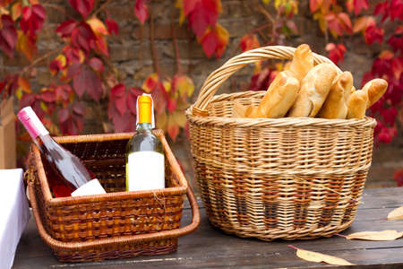 Two baskets with wine and bread in autumn photo