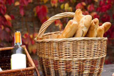 Twobaskets with wine and bread in autumn background. photo