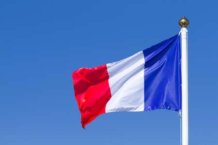 Flag of France waving on the blue sky Foto de archivo