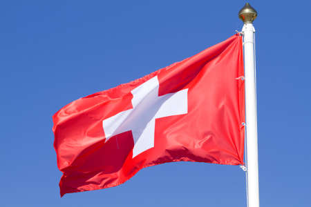 swiss culture: Flag of a Switzerland on a  blue sky