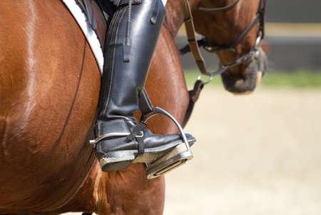 stirrup: Jockey riding boots in the stirrup Stock Photo