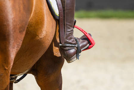 Jockey riding boot in the stirrup Stock Photo