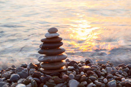 Stack of a stones on the sea beach at sunrise