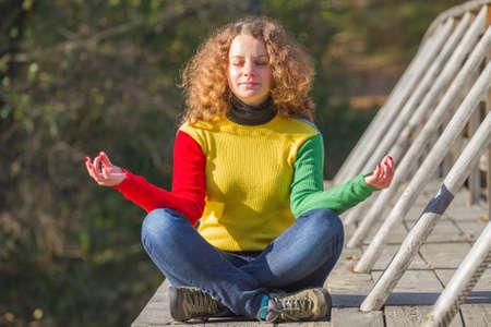 Girl meditates on the bridge in autumn Stock fotó