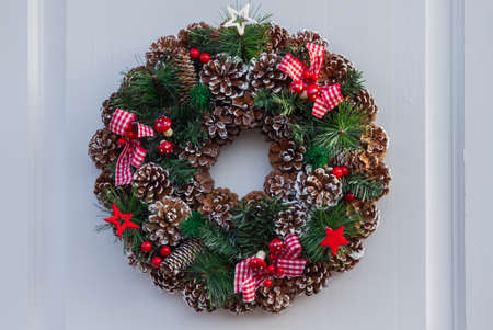 Christmas wreath with balls and ribbons on a white door