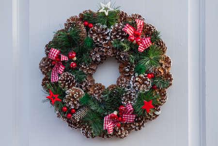 Corona de Navidad con bolas y cintas en una puerta blanca