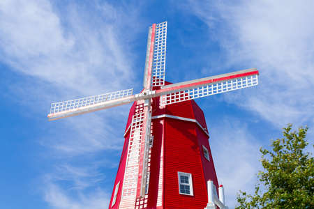 View of traditional red wooden windmill against a blue sky