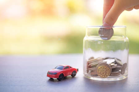 Red car toy and hand putting coins in a glass jar on abstract bright blurred background.