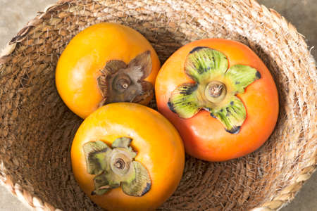 Close up, Fresh ripe persimmons in wicker basket