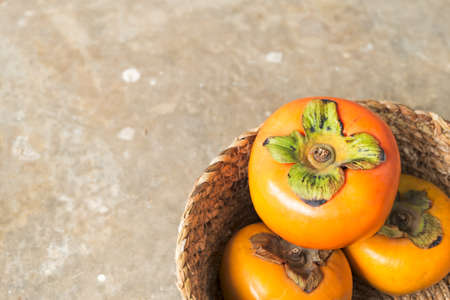 Fresh ripe persimmons in a wicker basket with copy space.