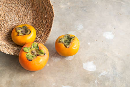 Fresh ripe persimmons with wicker basket on the floor