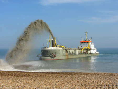 replenishing: Dredger replenishing beach at Eastbourne, England, after Winter storms Stock Photo