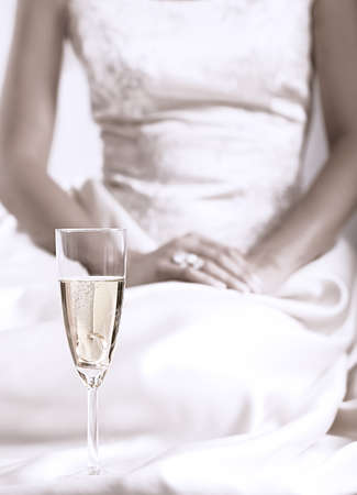 bubbly: glass of champagne with gold band and background nuncial girl